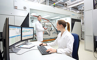 Two Employees check Test Data at a Test Station for PEM Fuel Cell Systems